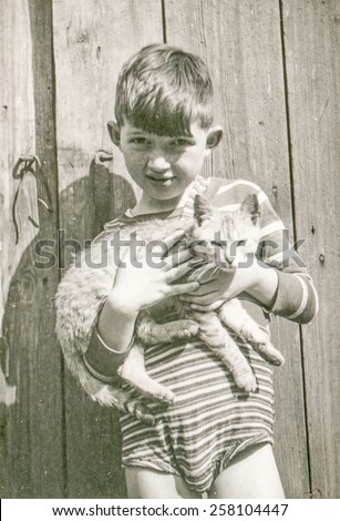 Vintage photo of little boy with a cat, 1950's - stock photo