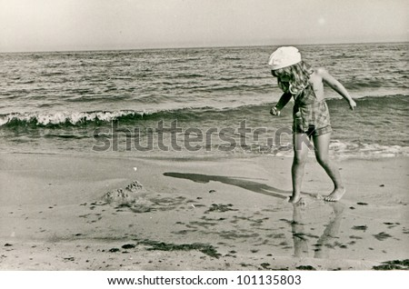Vintage photo of little girl on beach (fifties) - stock photo