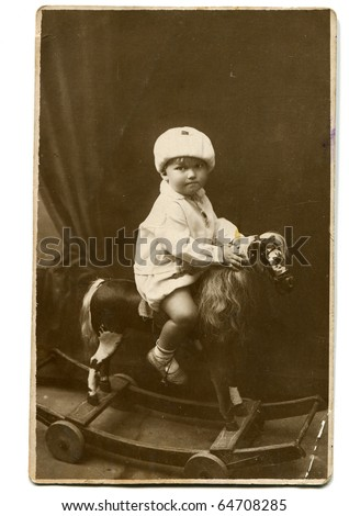 Vintage photo of little girl on rocking horse (circa 1928) - stock photo