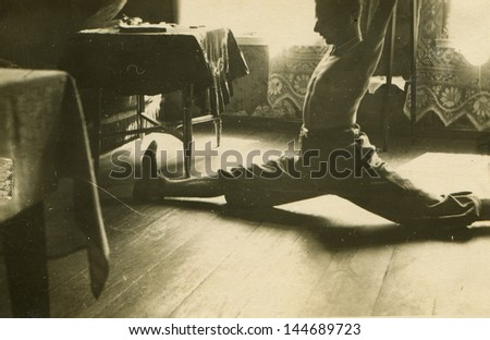 Vintage photo of man exercising a split, forties - stock photo