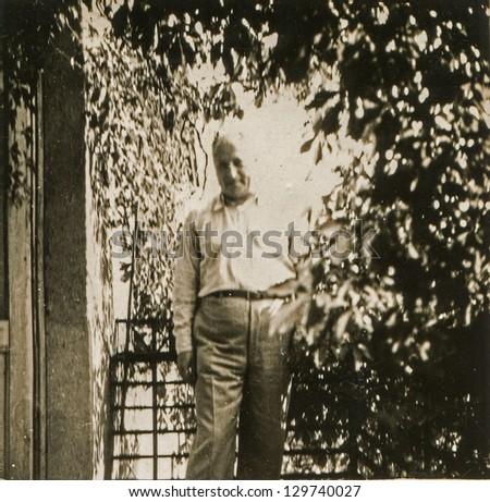 Vintage photo of man on balcony (fifties) - stock photo