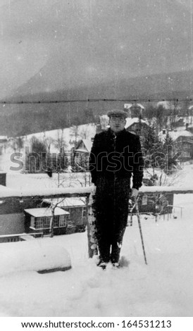 Vintage photo of man walking in snowny mountains, fifties - stock photo