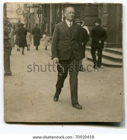 Vintage photo of man walking in the street (twenties/thirties) - stock photo