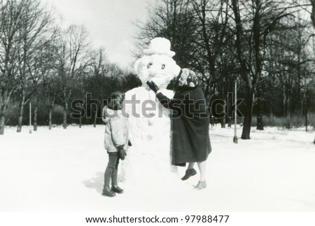 Vintage photo of mother and daughter building a snowman (fifties) - stock photo