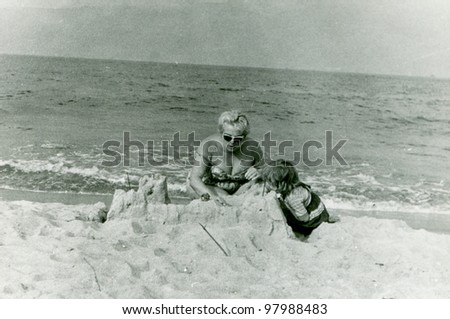 Vintage photo of mother and daughter building sand castle (fifties) - stock photo