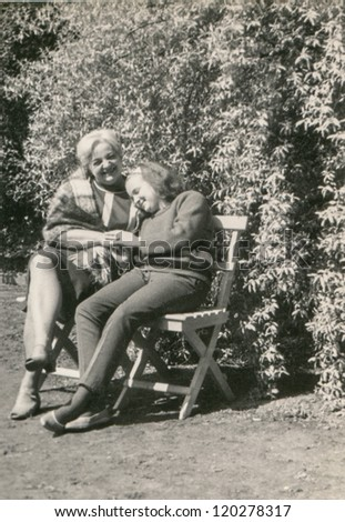 Vintage photo of mother and daughter in park (early sixties) - stock photo