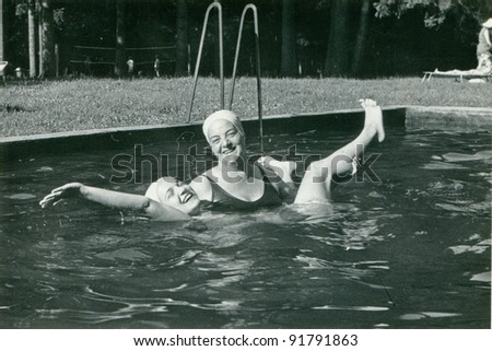 Vintage photo of mother and daughter in swimming pool (sixties) - stock photo