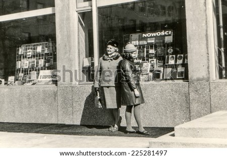 Vintage photo of mother and daughter looking bookshop window, sixties  - stock photo