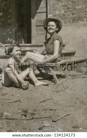 Vintage photo of mother and daughter sunbathing, fifties - stock photo