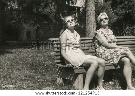 Vintage photo of mother and daughter tanning on bench in park (sixties) - stock photo