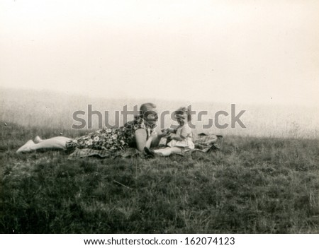 Vintage photo of mother and little daughter outdoor, fifties - stock photo