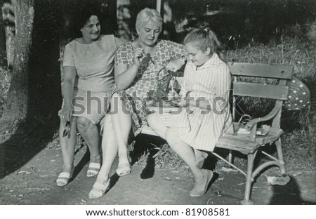 Vintage photo of mother, aunt and daughter playing darts (early sixties) - stock photo