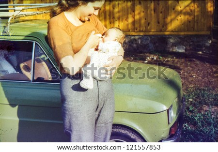 Vintage photo of mother breastfeeding her daughter (1981) - stock photo