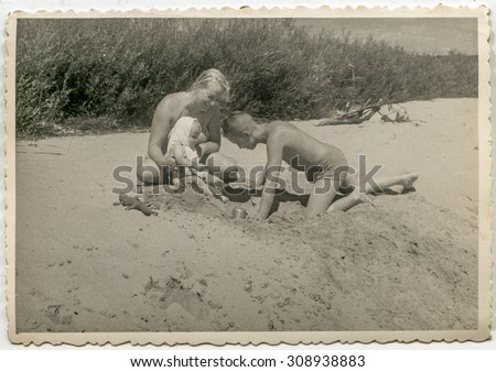 Vintage photo of mother playing on beach with her son and baby daughter, 1955 - stock photo