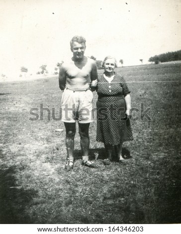 Vintage photo of mother with adult son, sixties - stock photo
