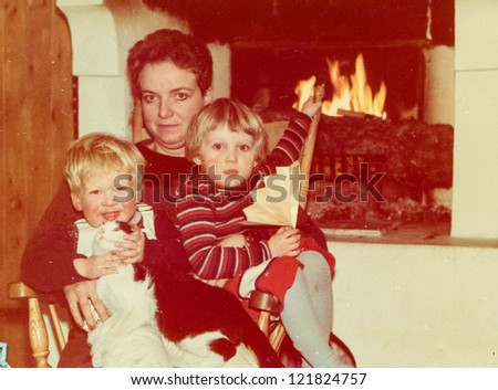 Vintage photo of mother with little children and cat near fireplace (early eighties) - stock photo
