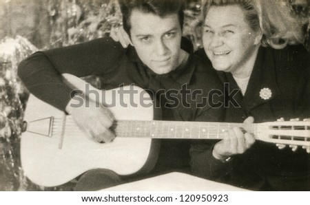 Vintage photo of mother with son playing guitar (sixties) - stock photo