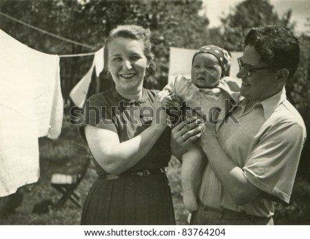 Vintage photo of parents with daughter (fifties) - stock photo