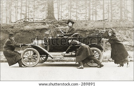 Vintage Photo of People Pushing Old Car - stock photo