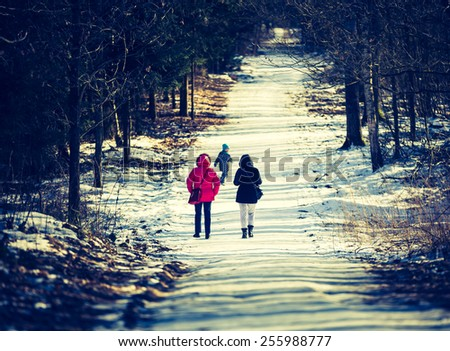 vintage photo of people walking in winter forest with child - stock photo