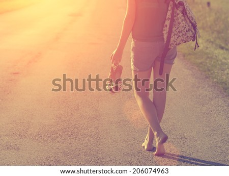 Vintage photo of sexy traveler barefoot woman walking on highway - stock photo