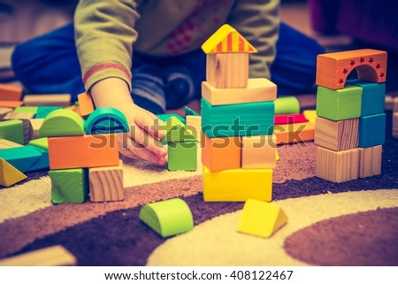 Vintage photo of small child playing with wooden blocks. Caucasian boy building with blocks - stock photo