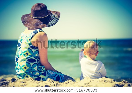 Vintage photo of small child with mother on sea shore. Beautiful landscape with baby and mother photographed from behind - stock photo