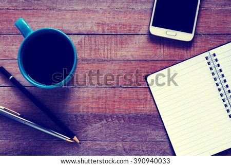 Vintage photo of top view on opened notebook, smartphone, pen and cup of coffee on rustic office desk. - stock photo