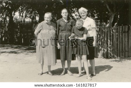 Vintage photo of two grandmothers, mother and daughter with a chicken on farm, fifties - stock photo