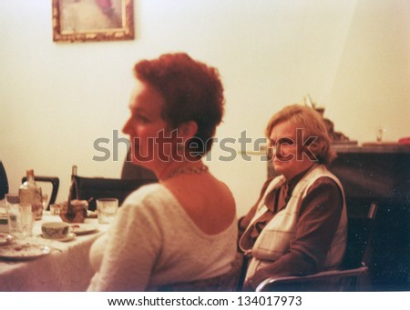 Vintage photo of two woman, one elderly and one young, during a family party (seventies) - stock photo