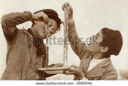 Vintage Photo of two young boys eating spaghetti with their hands - stock photo