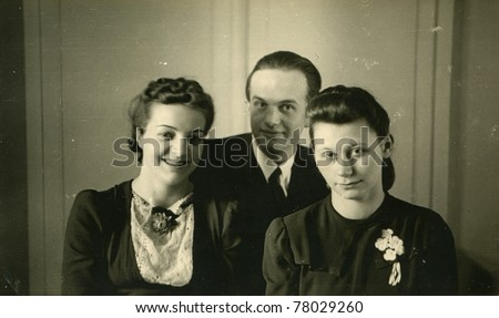 Vintage photo of two young women and a man (thirties) - stock photo