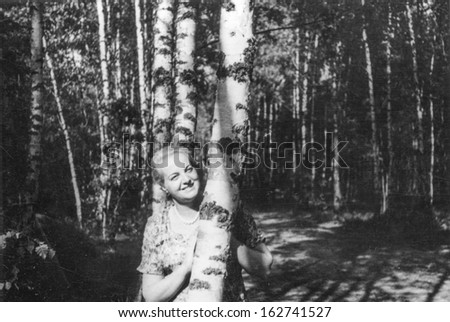 Vintage photo of woman in forest, fifties - stock photo