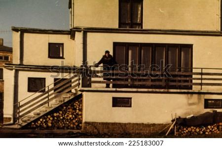 Vintage photo of woman on balcony, early eighties - stock photo