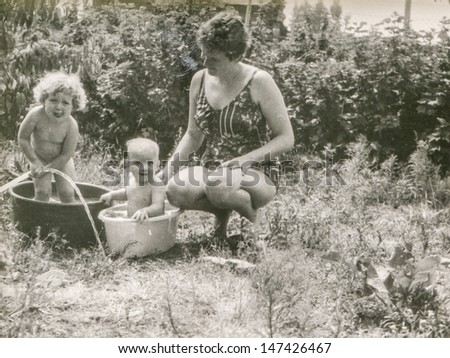 Vintage photo of woman washing two children in washtubs, eighties - stock photo