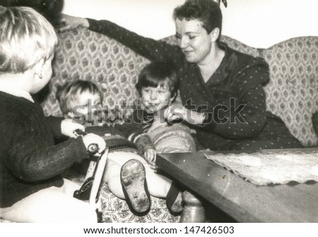 Vintage photo of woman with three children, eighties - stock photo