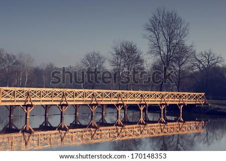 Vintage photo of wooden bridge over river - stock photo