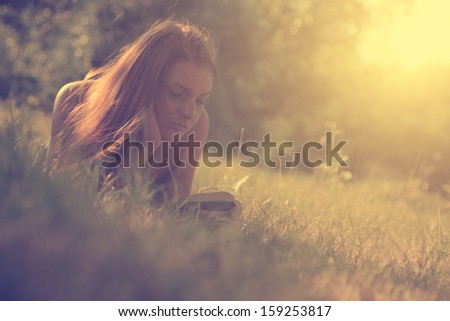 Vintage photo of young girl lying in the grass and reading book - stock photo