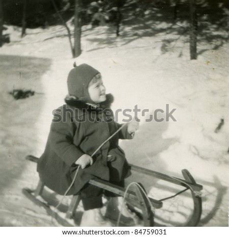 Vintage photo of young girl on sled (fifties) - stock photo