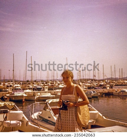 Vintage photo of young girl with a camera in Saint Tropez port, seventies - stock photo