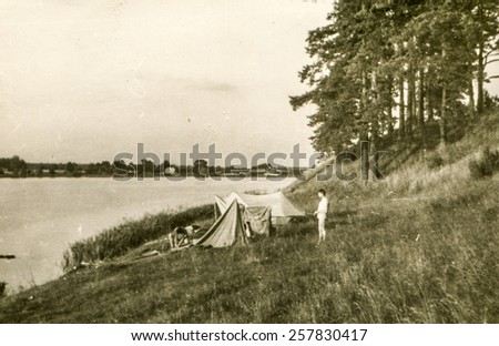 Vintage photo of young man camping during a canoe trip (1960's) - stock photo