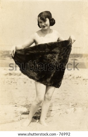 Vintage photo of young woman at beach hiding behind towel - stock photo