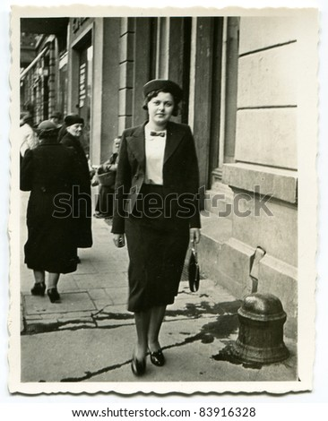 Vintage photo of young woman walking on the street (thirties) - stock photo