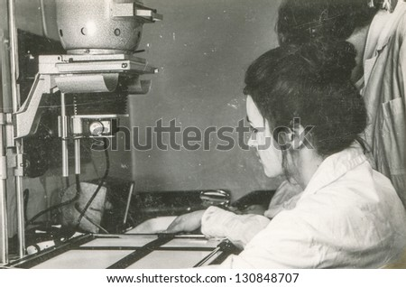 Vintage photo of young woman working in laboratory, seventies - stock photo