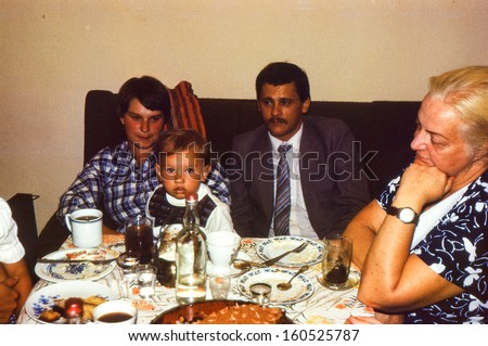 Vintage photo (scanned reversal film) - family dinner, early eighties - stock photo