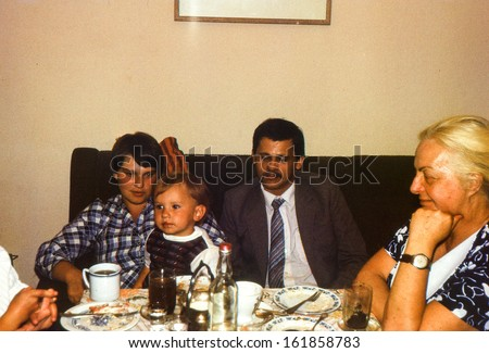 Vintage photo (scanned reversal film) - - family dinner, early eighties - stock photo
