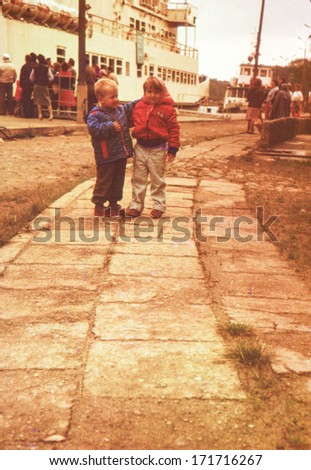 Vintage photo (scanned reversal film) of brother and sister in port (early eighties) - stock photo