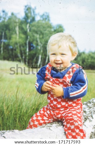 Vintage photo (scanned reversal film) of little girl outdoor (early eighties) - stock photo