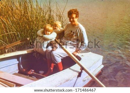 Vintage photo (scanned reversal film) of mother with little children on rowing boat, early eighties - stock photo