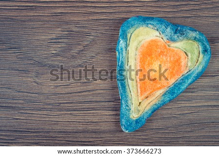 Vintage photo, Valentine colorful heart made of salt dough on wooden background, decoration for Valentines Day, symbol of love, copy space for text - stock photo